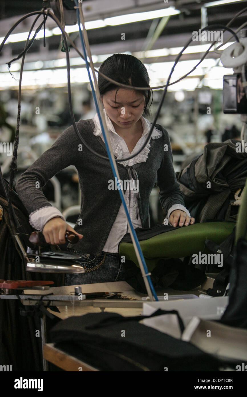 Workers iron garments for the 'Venetia' brand - Stock Image