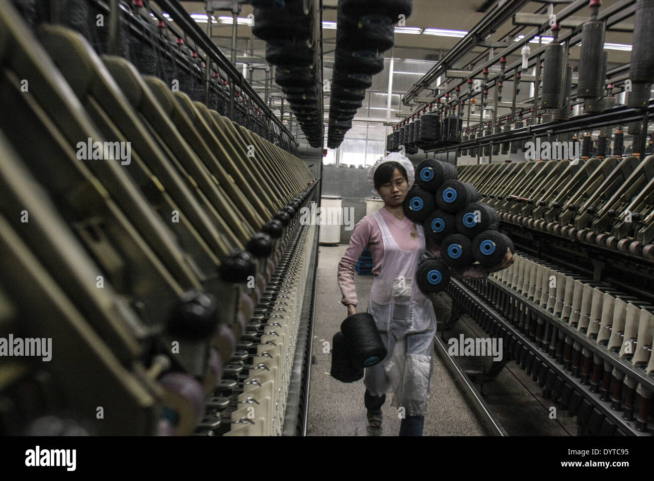 Workers operate a weaving machine at the Jiangsu Sunshine Co - Stock Image