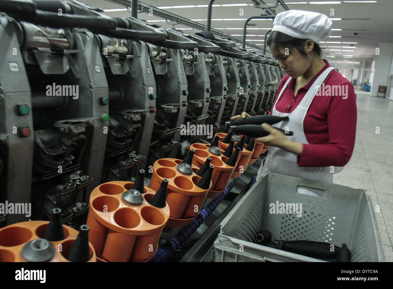 Workers operate a weaving machine at the Jiangsu Sunshine Co - Stock Image