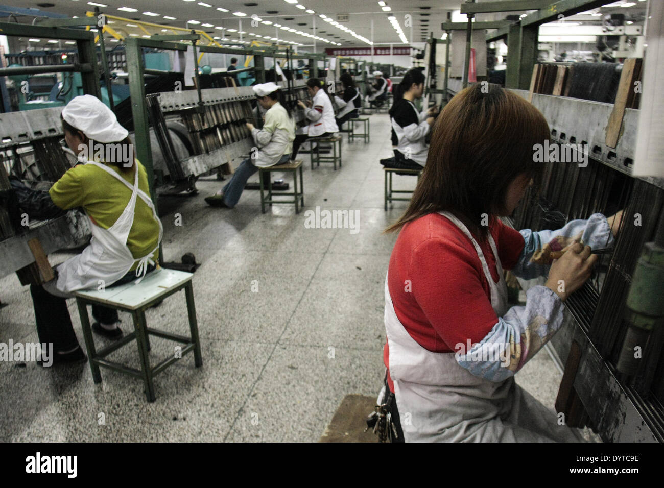 Workers operate a weaving machine at the Jiangsu Sunshine Co Stock Photo