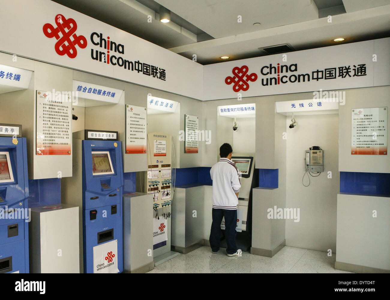 A man charges his cell phone at a self-service station of China Unicom Ltd Stock Photo
