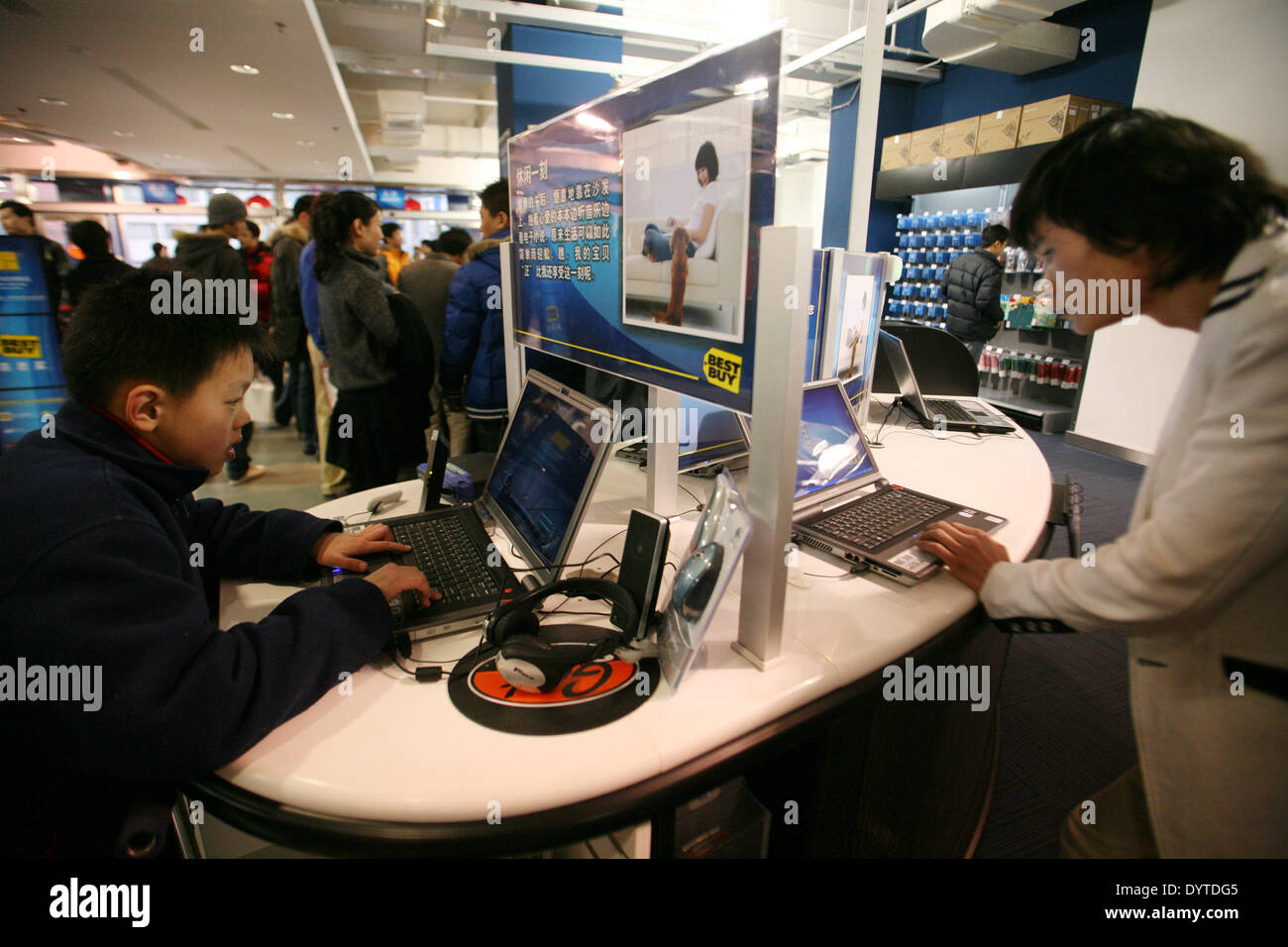 Customers try out laptops inside a Best Buy store in Shanghai - Stock Image