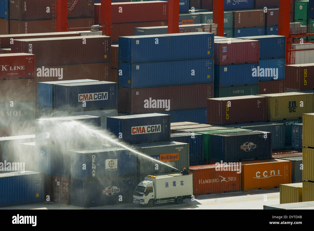 Workers spray disinfectant to containers at Yangshan Deep Water Port - Stock Image