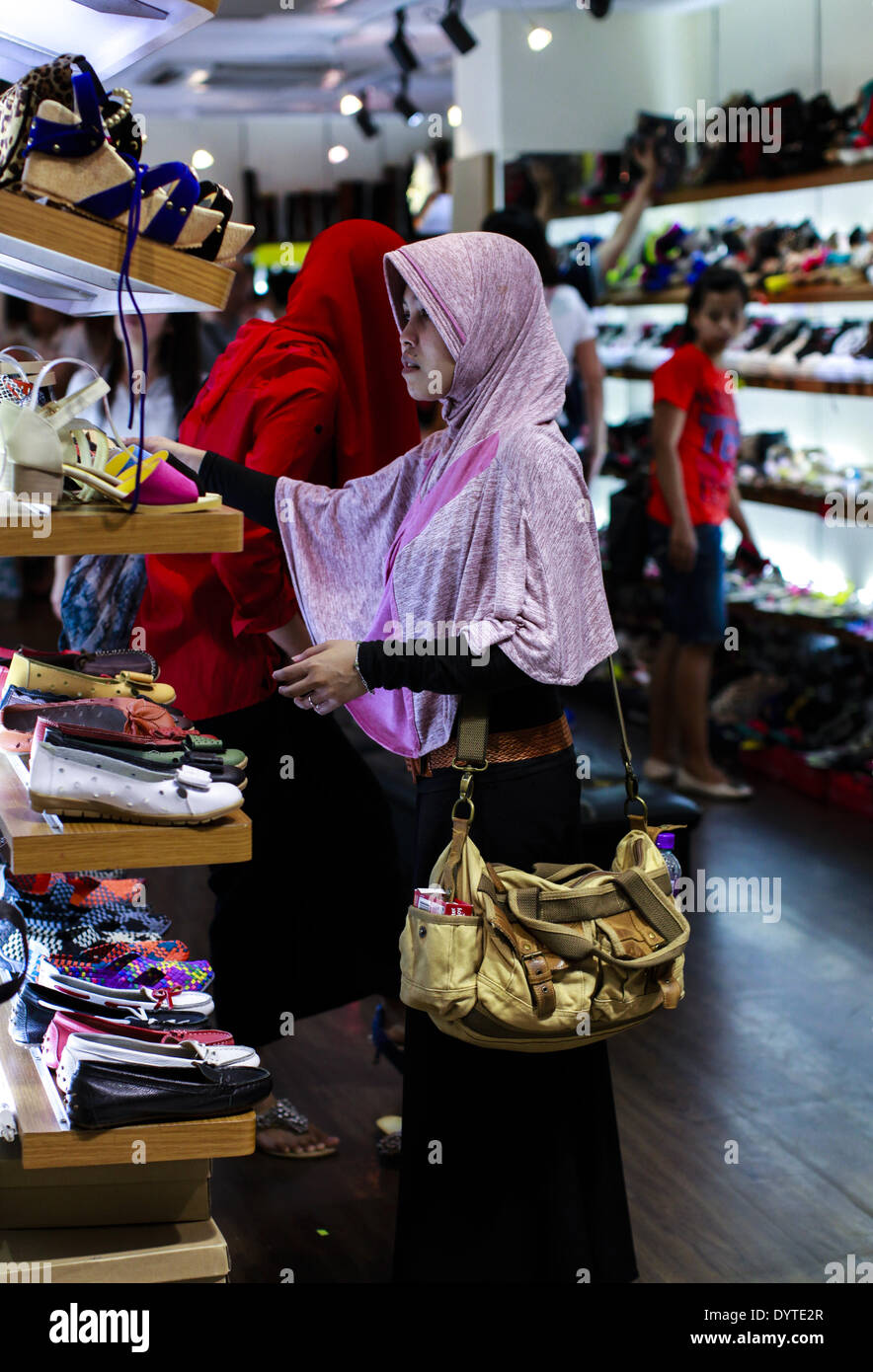 An off duty Indonesia home helper choose shoes at a market - Stock Image