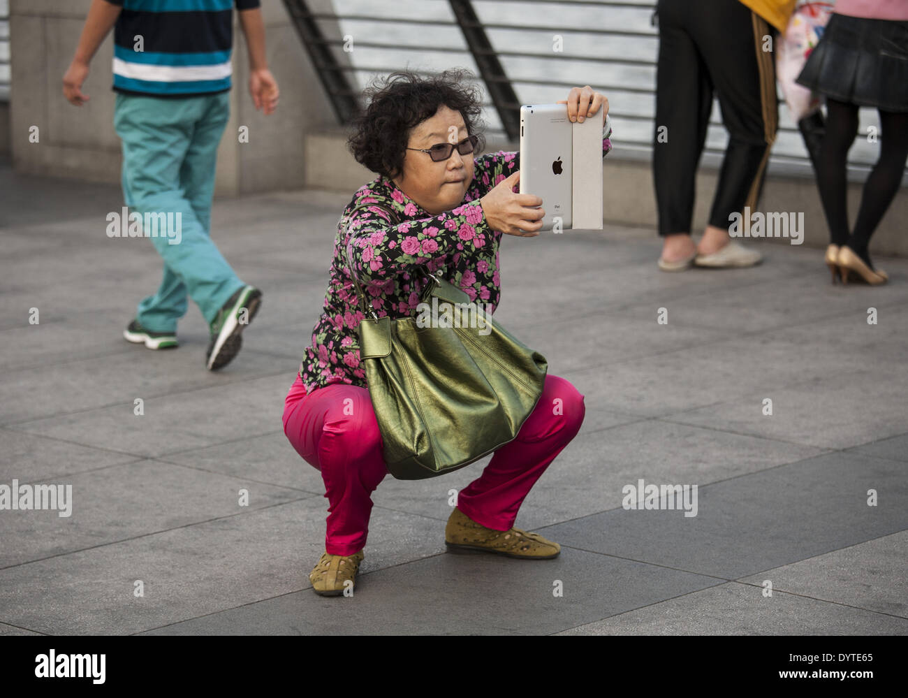 A woman use an iPad to take pictures at the Bund - Stock Image