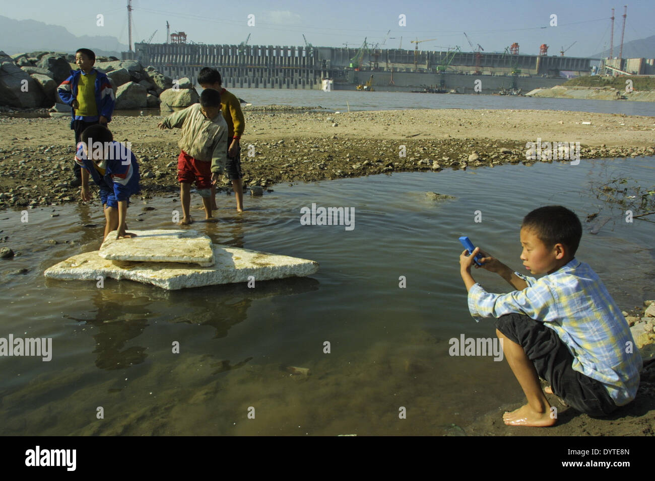 Kids of nearby village play besides the under constructed Three Gorges dam - Stock Image