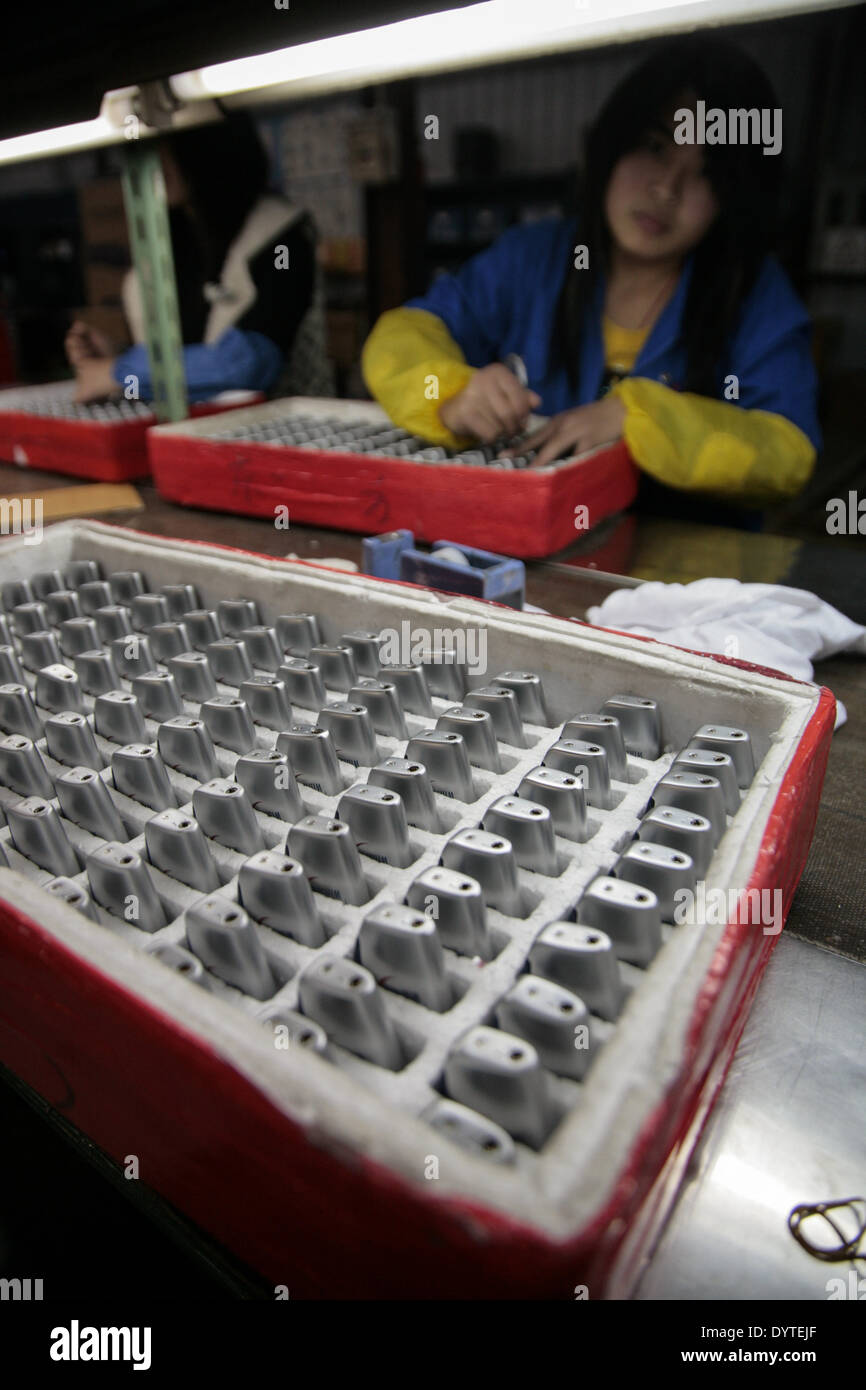 Workers make lighters at a factory - Stock Image