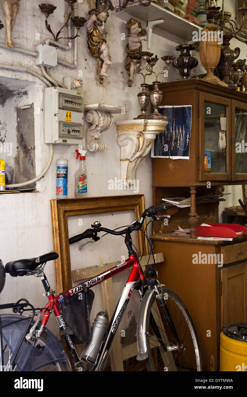 Bicycle leaning against wall in workshop with salvage items Stock Photo