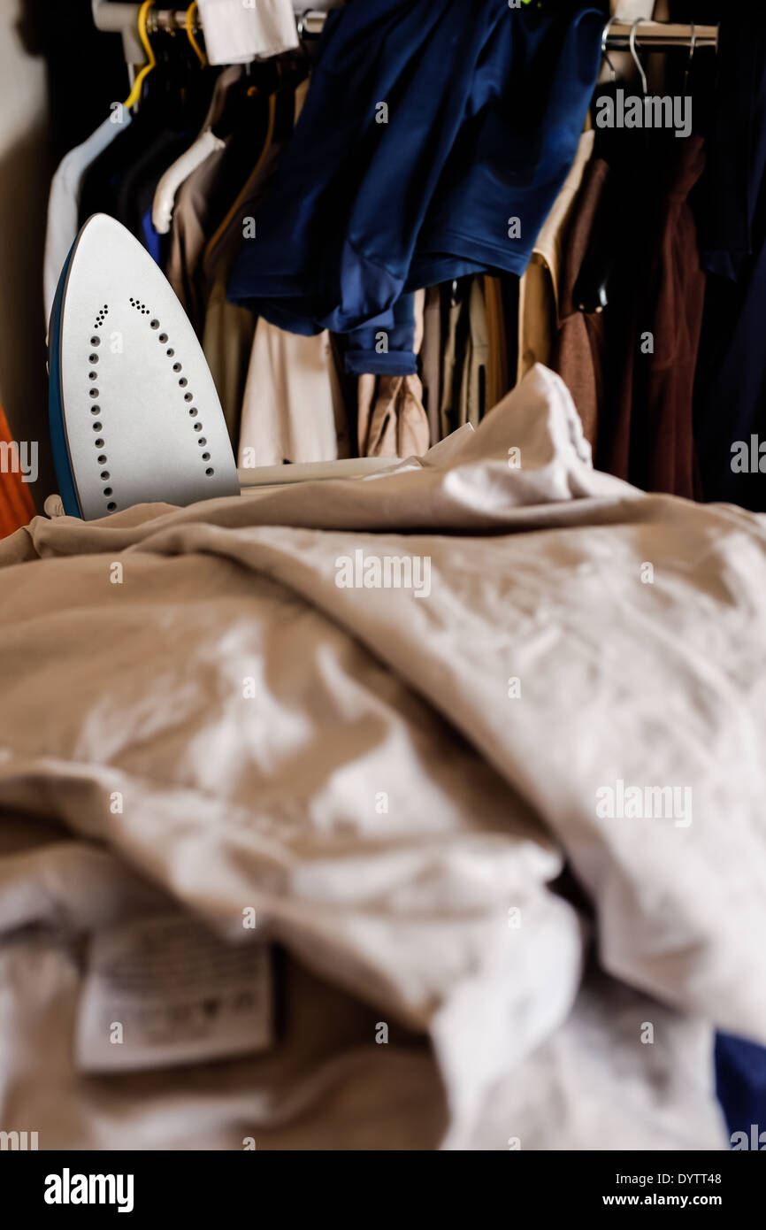A pile of bedlinen for ironing with an electric iron visible amongst the linen. - Stock Image