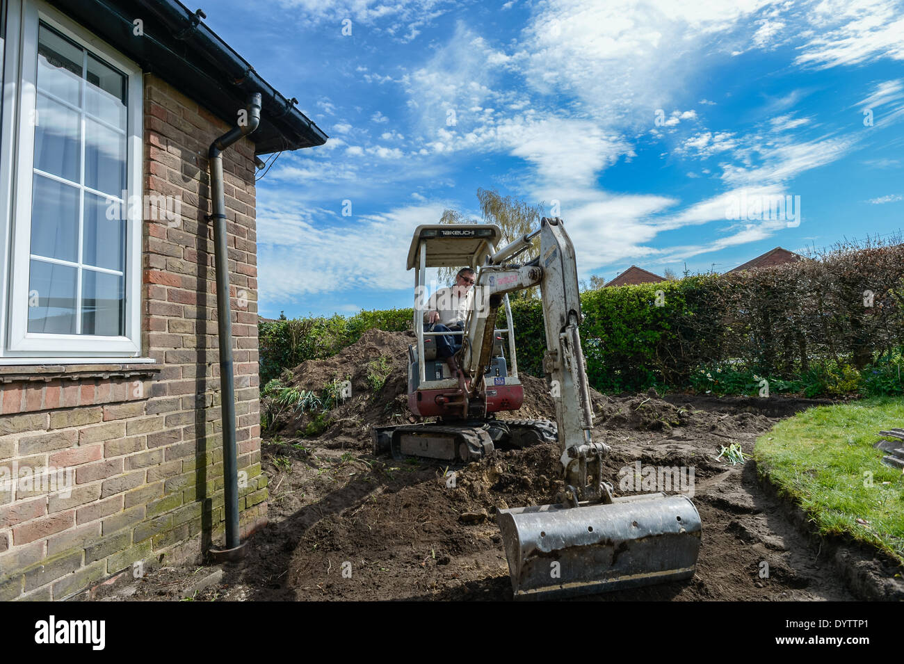 Excavating a lawn prior to laying a driveway using a micro compact excavator mechanical digger on a home improvement project. - Stock Image