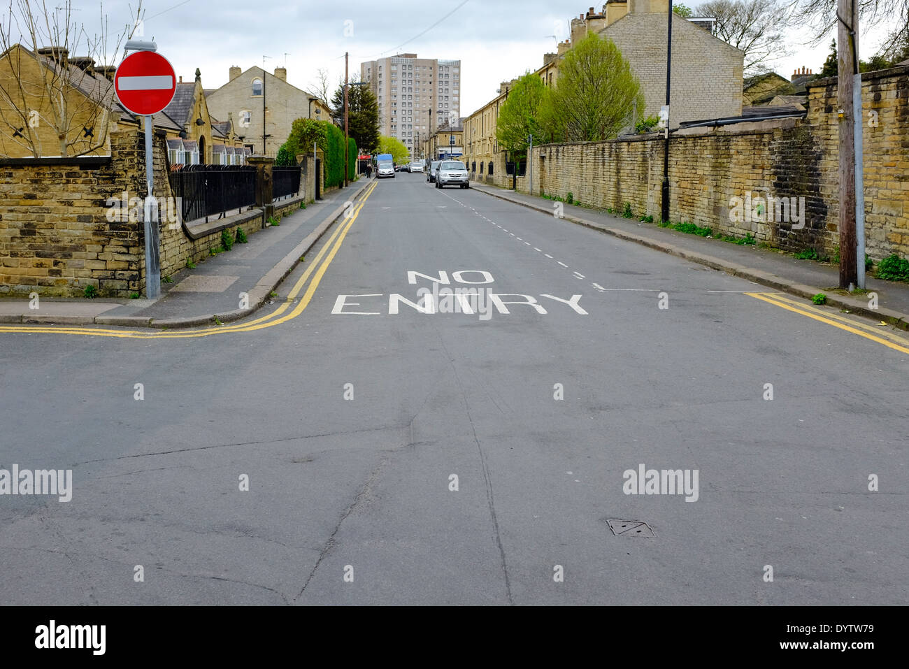 'No Entry' - a sign and notice on a road in an urban side street. A pedestrian is in the far distance. - Stock Image
