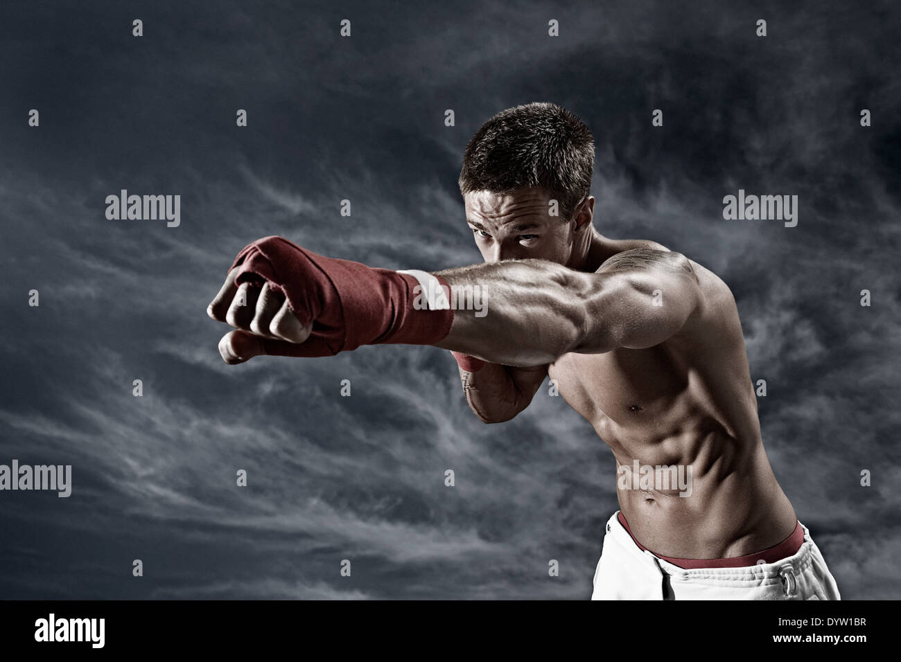 Martial artist throwing a punch backgrounded by stormy sky Stock Photo