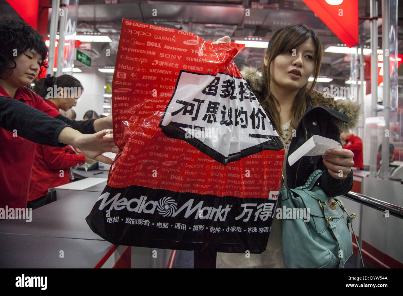 A customer carries a branded shopping bag as he exits a Media Markt store in Shanghai - Stock Image