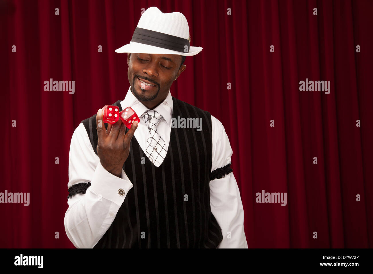 well dressed gambler in a retro suit holding over sized dice - Stock Image