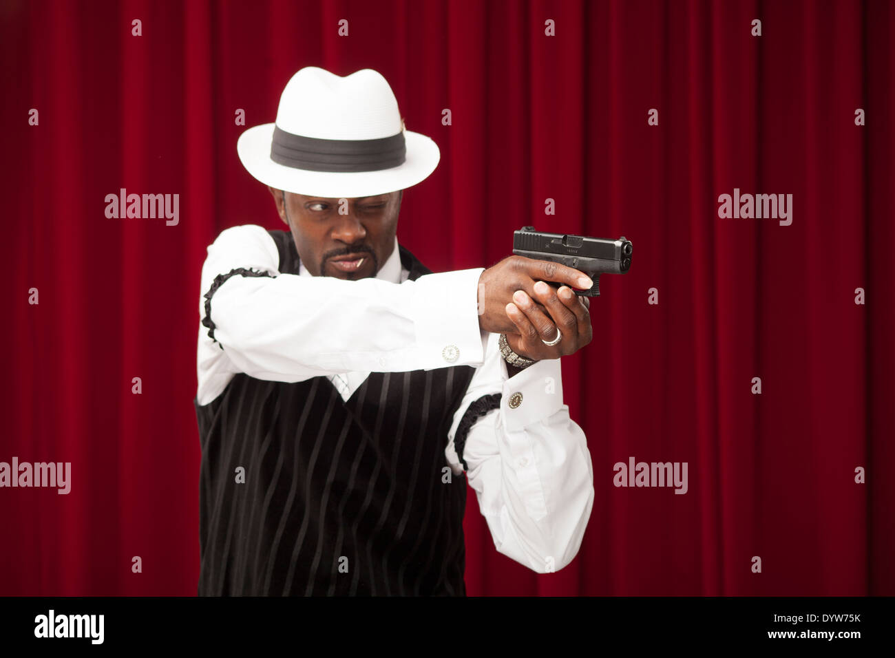 well dressed gambler in a retro suit pointing a gun - Stock Image