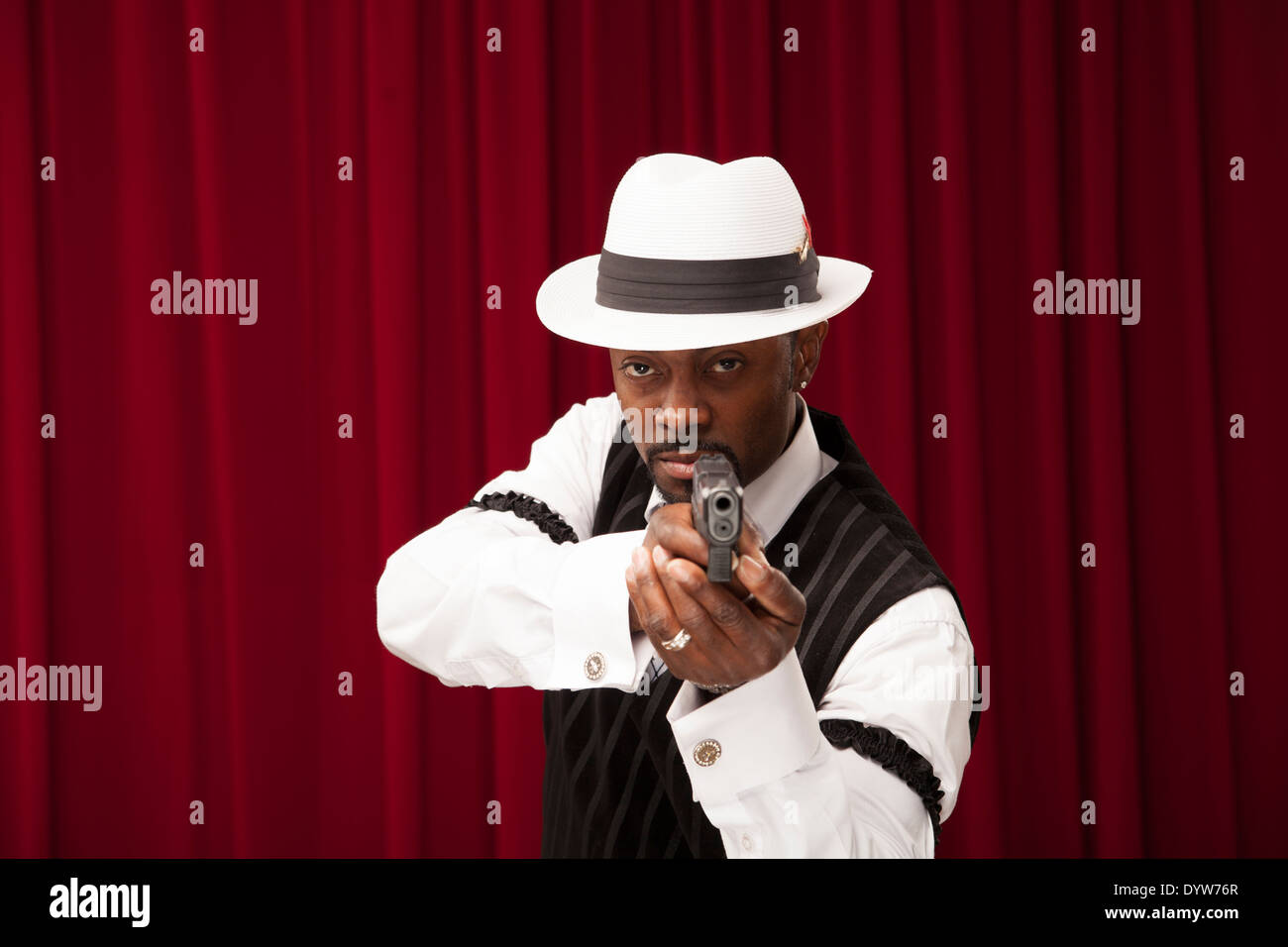 african american gambler dressed in retro mobster suit pointing gun - Stock Image