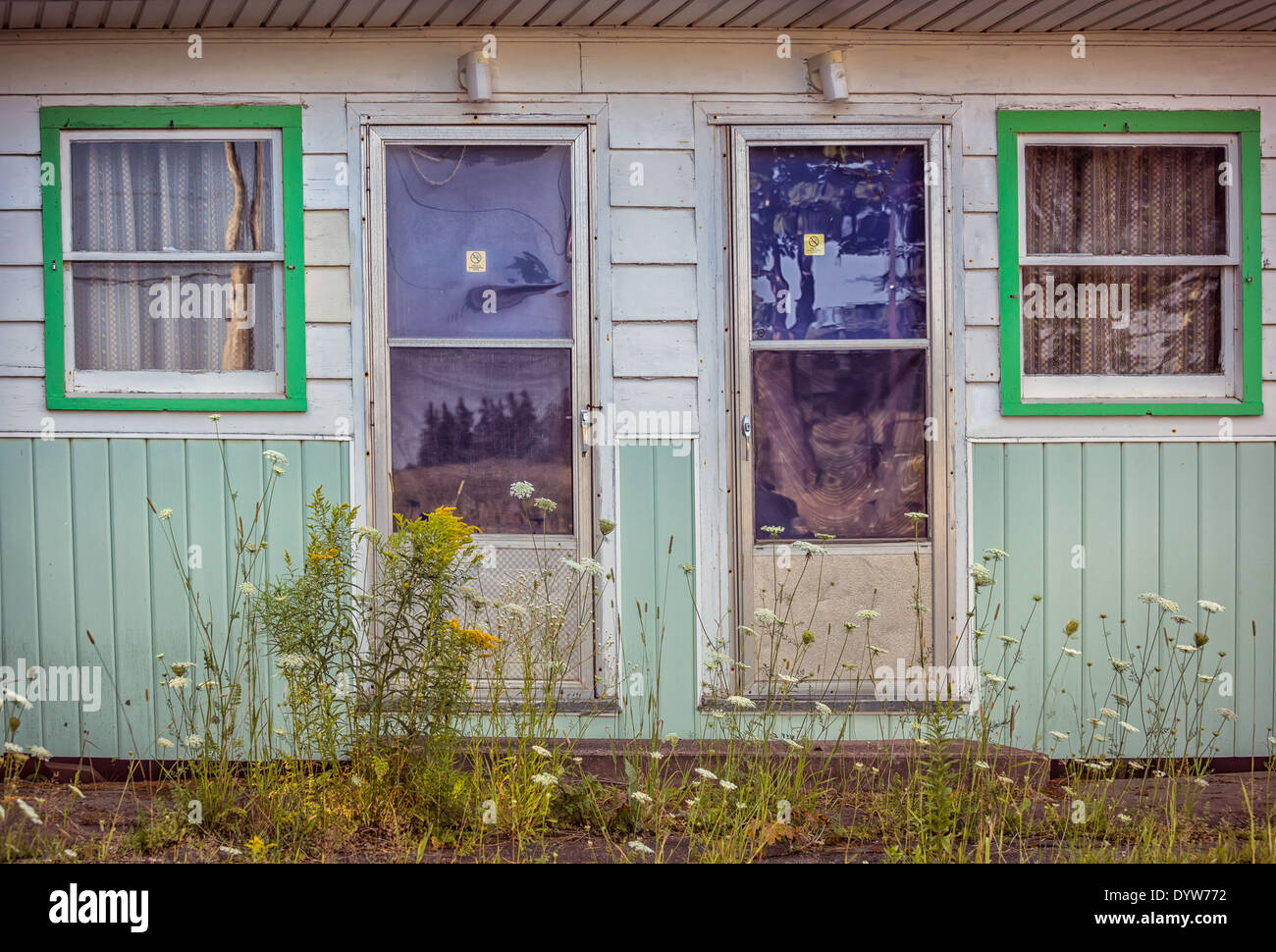 Retro abandoned motel growing up in weeds. - Stock Image