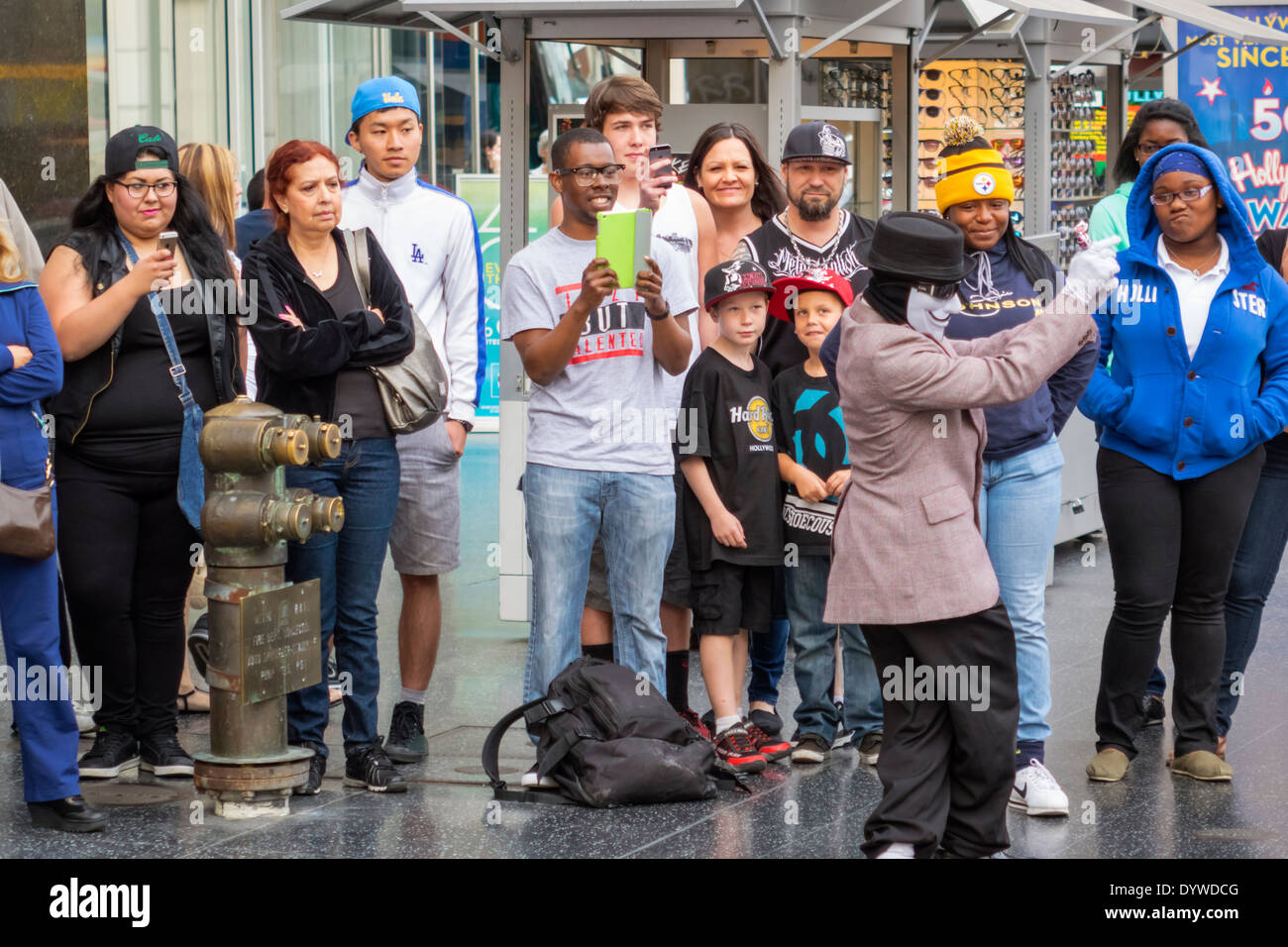 California CA LA Los Angeles Hollywood Boulevard movie industry Hollywood Walk of Fame street performer costume Anonymous mask audience mime Black Asi - Stock Image