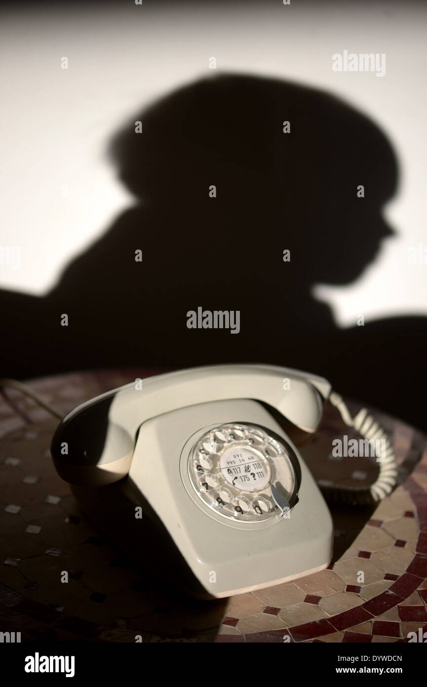 Berlin, Germany, old telephone and silhouette of a child on the wall - Stock Image