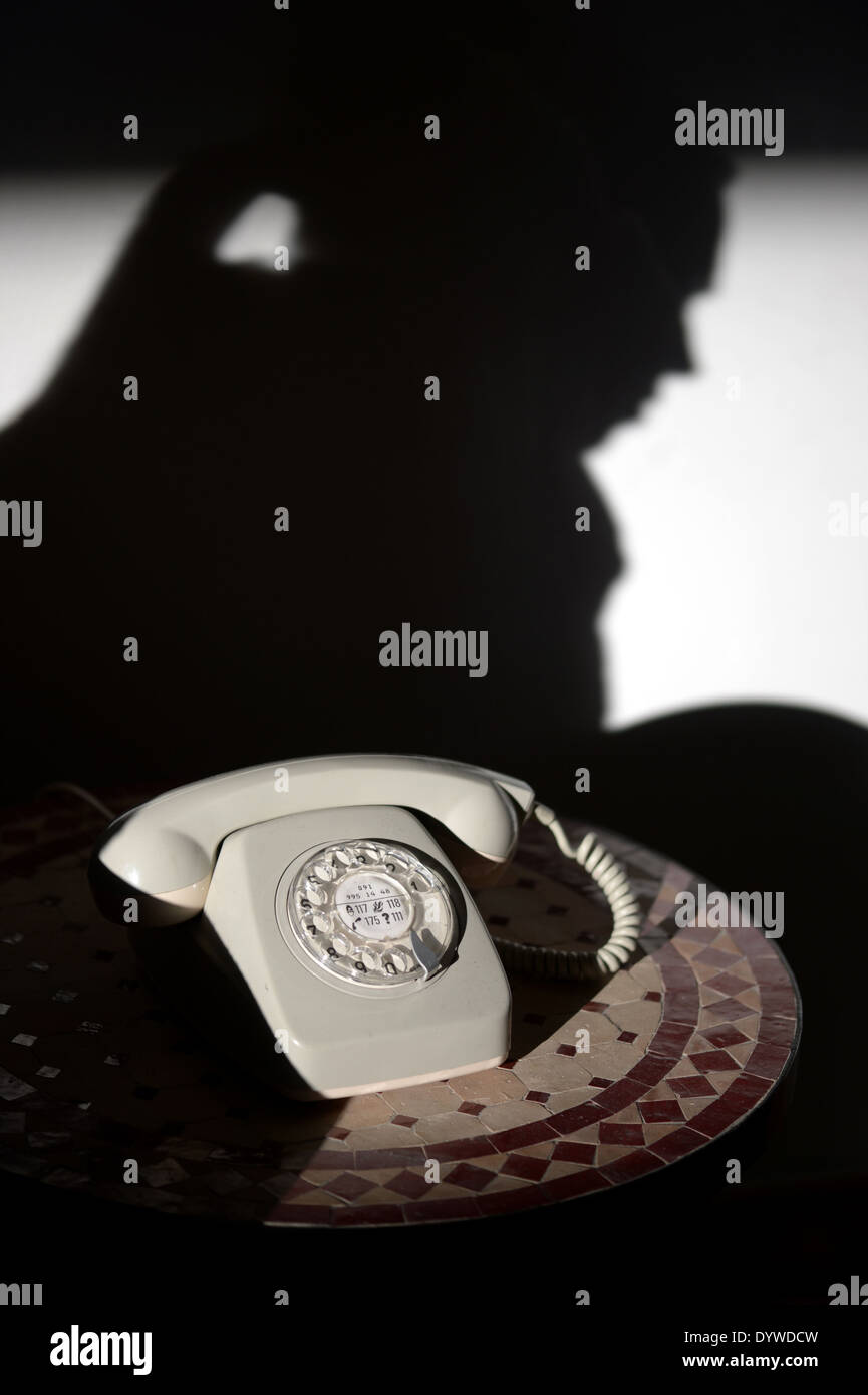 Berlin, Germany, old telephone set and silhouette of a woman on the wall - Stock Image
