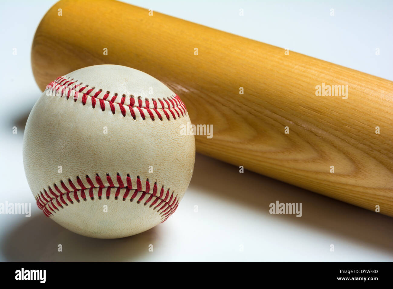 A wooden baseball bat and ball on a white background - Stock Image