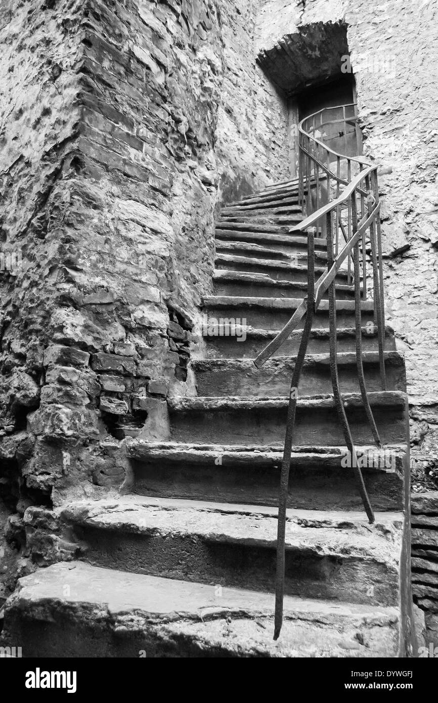 An old ancient stone made twisted stair leads up to a small door in stone wall. Photo taken in the Old Town of Tallinn, Estonia - Stock Image