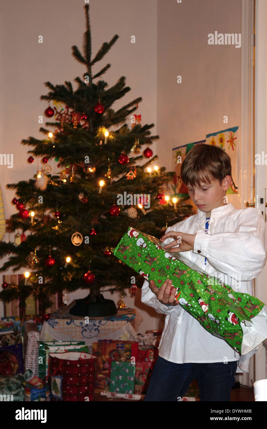 Berlin, Germany, boy grabs on Christmas Eve from his gift - Stock Image