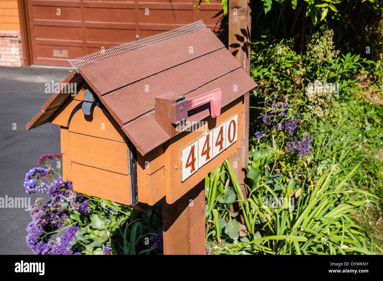 A house shaped wooden mailbox with bird deterrent on top and address on the side at a residence in Santa Barbara County, CA, USA - Stock Image