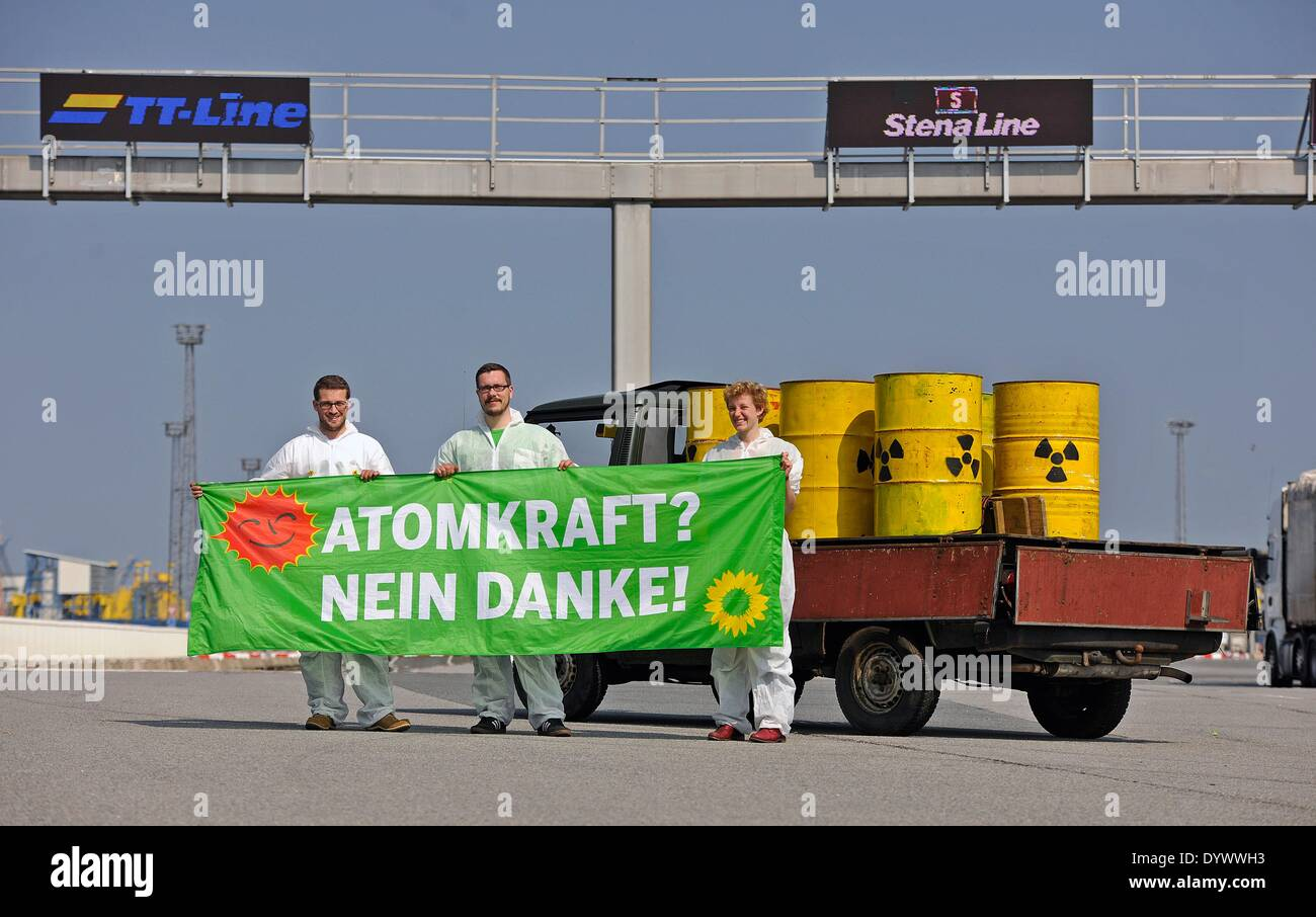 Rostock, Germany. 26th Apr, 2014. Members of the party Alliance '90/The Greens stand at the Rostock harbour ferry terminal with a symbolic nuclear waste transporter and a banner which reads 'nuclear power, no thanks' to protest the transportation of nuclear material through the harbour in Rostock, Germany, 26 April 2014. The demonstration is part of nationwide events to commemorate the 28th anniversary of the Chernobyl disaster. Photo: THOMAS HAENTZSCHEL/dpa/Alamy Live News - Stock Image