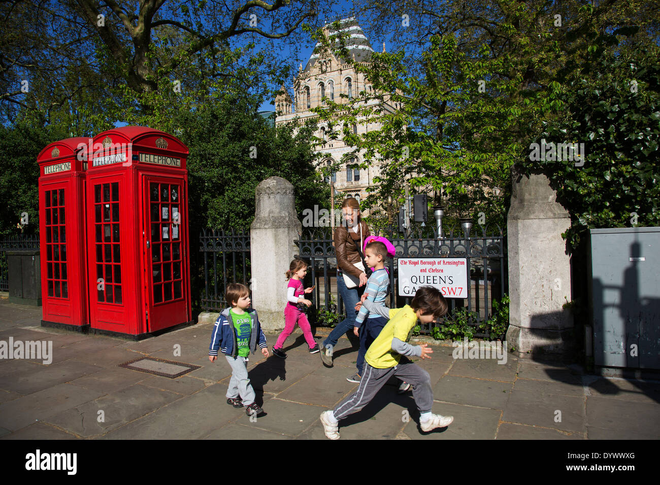 Family playing in the street by two red telephone boxes outside the Natural History Museum in South Kensington. London, UK. - Stock Image