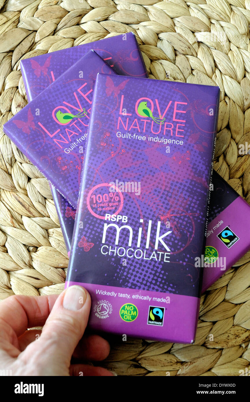 Hand reaching for ethical organic Fairtrade Fair Trade chocolate no palm oil  RSPB Royal Society for the Protection of  Birds - Stock Image