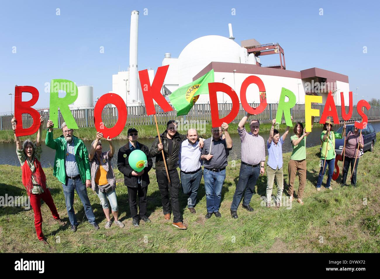 Brokdorf, Germany. 26th Apr, 2014. Protesters, among them Rebecca Harms (front L), top candidate of Alliance '90/The Greens, form the words 'save the energy transition' with colourful letters in front of the nuclear power plant in Brokdorf, Germany, 26 April 2014. Several hundred people commemorate the 28th anniversary of the Chernobyl disaster and demand the closing of the Brokdorf nuclear plant. Photo: BODO MARKS/dpa/Alamy Live News - Stock Image