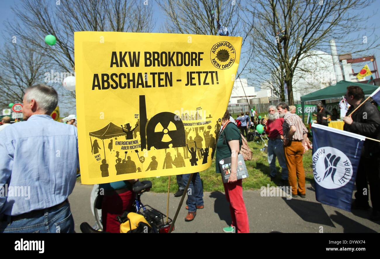 Brokdorf, Germany. 26th Apr, 2014. Protesters with a sign which reads 'Close the Brokdorf nuclear plant now' rally in front of the nuclear power plant in Brokdorf, Germany, 26 April 2014. Several hundred people commemorate the 28th anniversary of the Chernobyl disaster and demand the closing of the Brokdorf nuclear plant. Photo: BODO MARKS/dpa/Alamy Live News - Stock Image