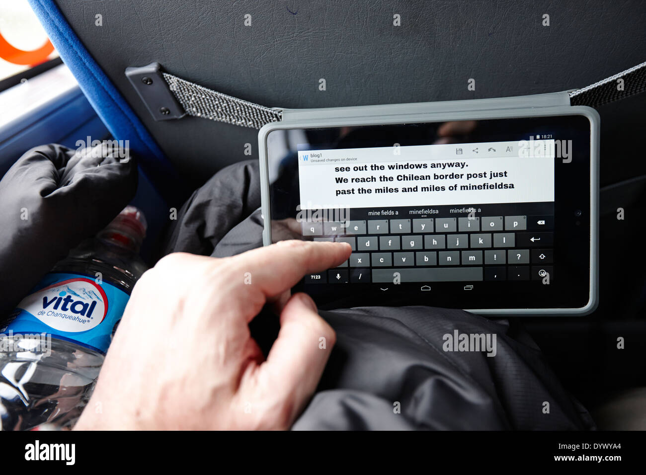 man using tablet computer to write blog whilst travelling on a bus in south america - Stock Image