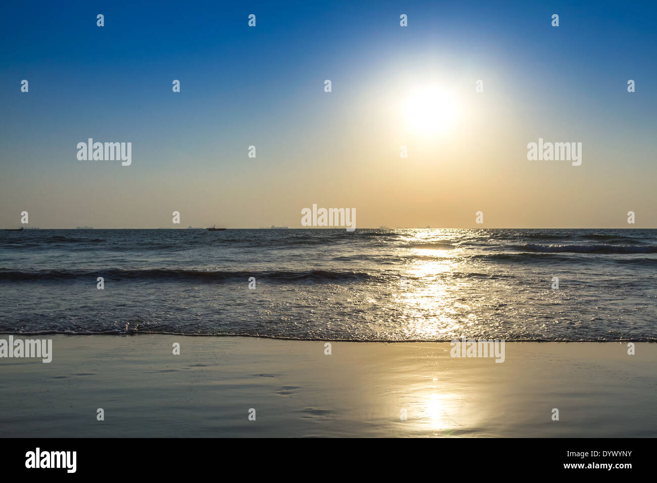 Scenic view from beach in Goa to beautiful sunrise above the Arabian sea. Sun reflection on sea surface - Stock Image