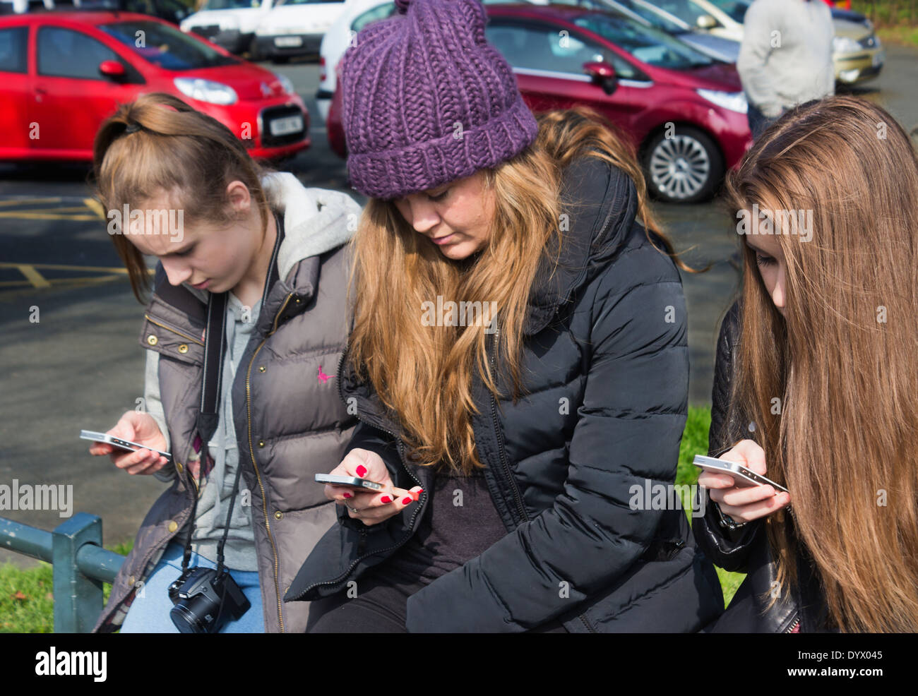 Three girls looking at mobile telephones. - Stock Image