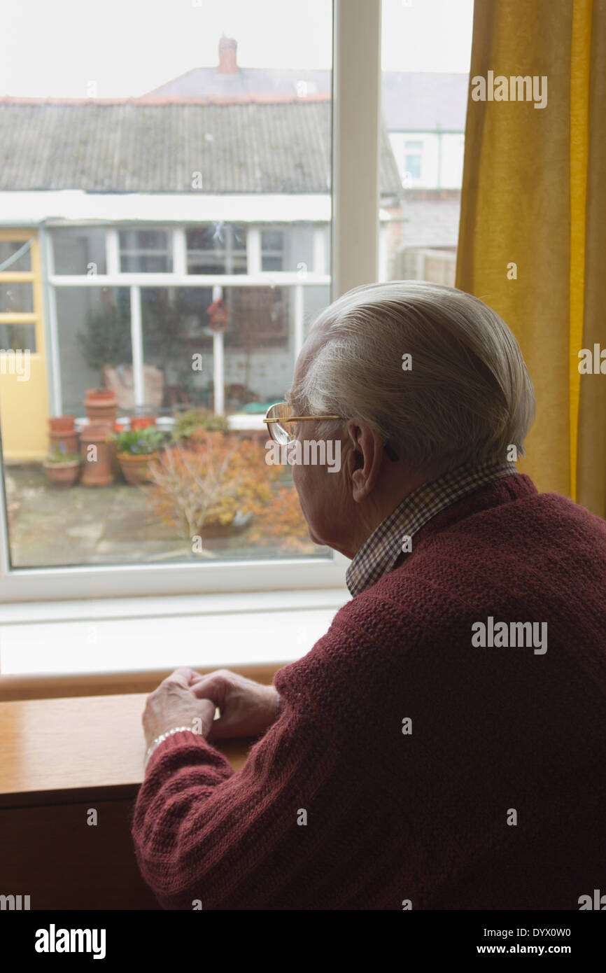 Lonely old man looking out of window at garden. - Stock Image