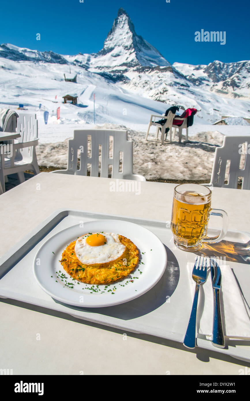Rosti with fried egg, a traditional swiss dish, with Matterhorn in the background, Zermatt, Wallis or Valais, Switzerland - Stock Image