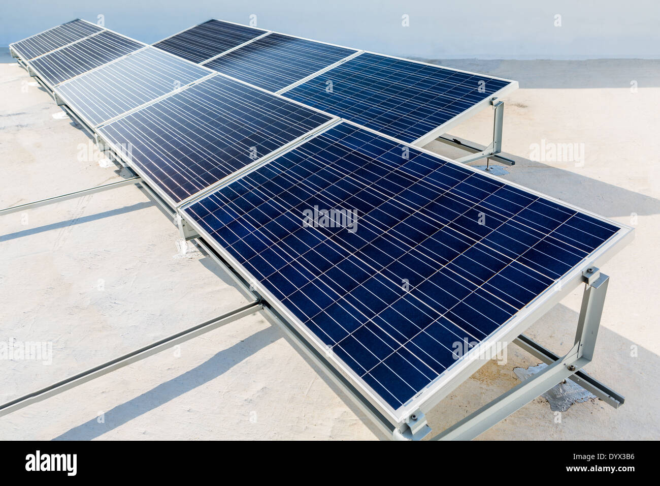 Solar panels standing on a rooftop under a bright sunny day - Stock Image