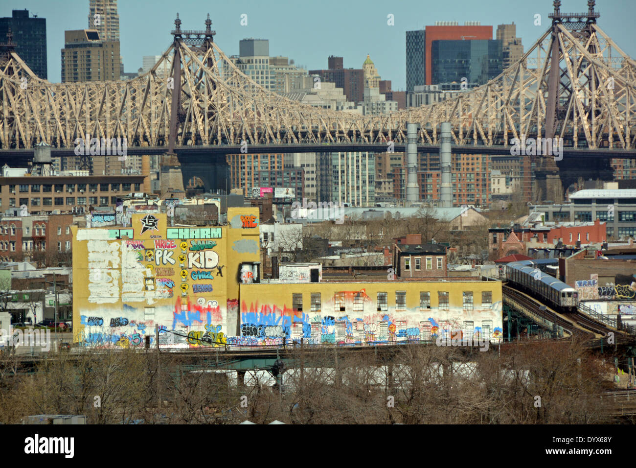 5 Pointz graffiti museum with the 59th Street Bridge and Manhattan skyline in the background and the subway in the foreground. - Stock Image