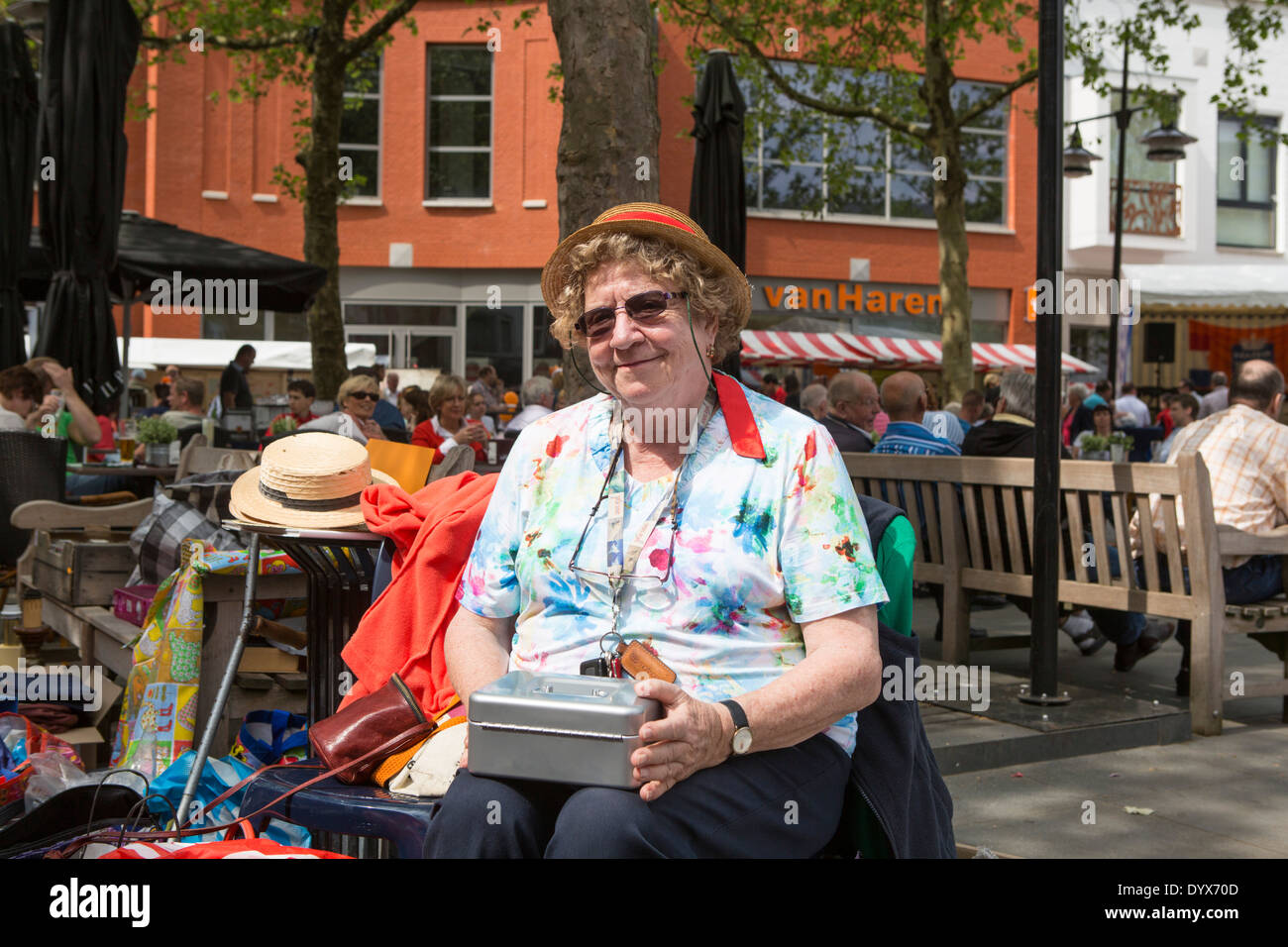 Woman taking care of the money at the free market of Helmond in the Netherlands at King's day. - Stock Image