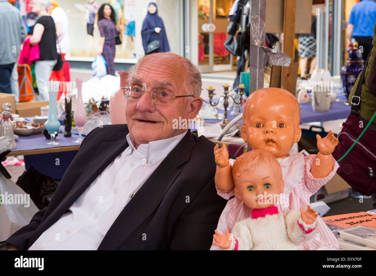 Portrait of an old man with two dolls at the free market at King's Day in Helmond in the Netherlands - Stock Image