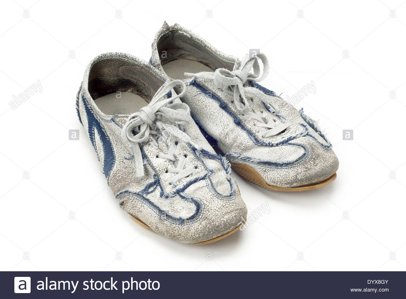 A pair of worn out trainers isolated on white - Stock Image