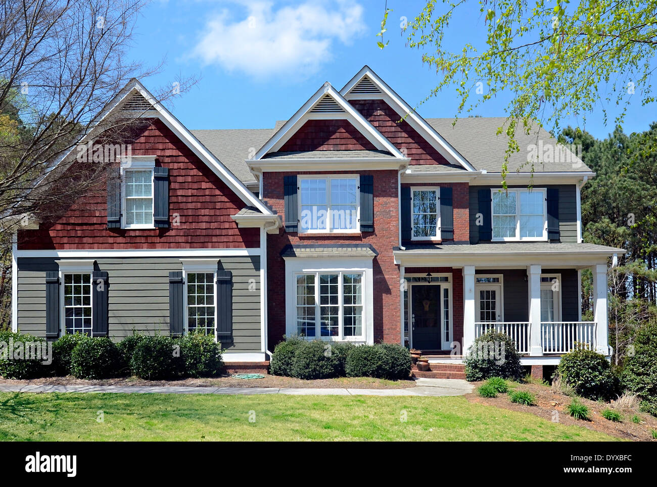 The front of a two story house with brick and siding, in the early spring. - Stock Image
