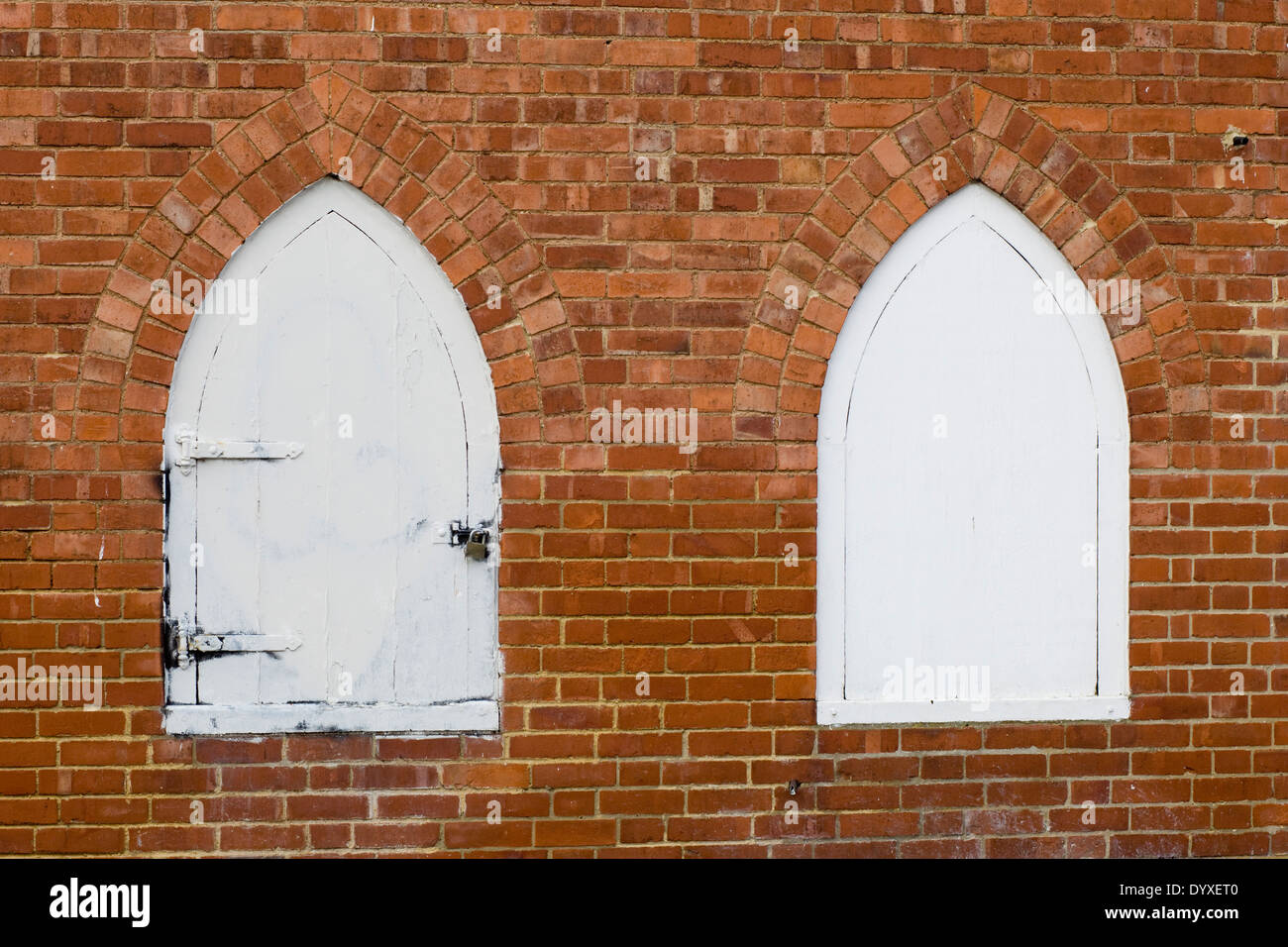 Two White Arched doors on a red brick wall - Stock Image