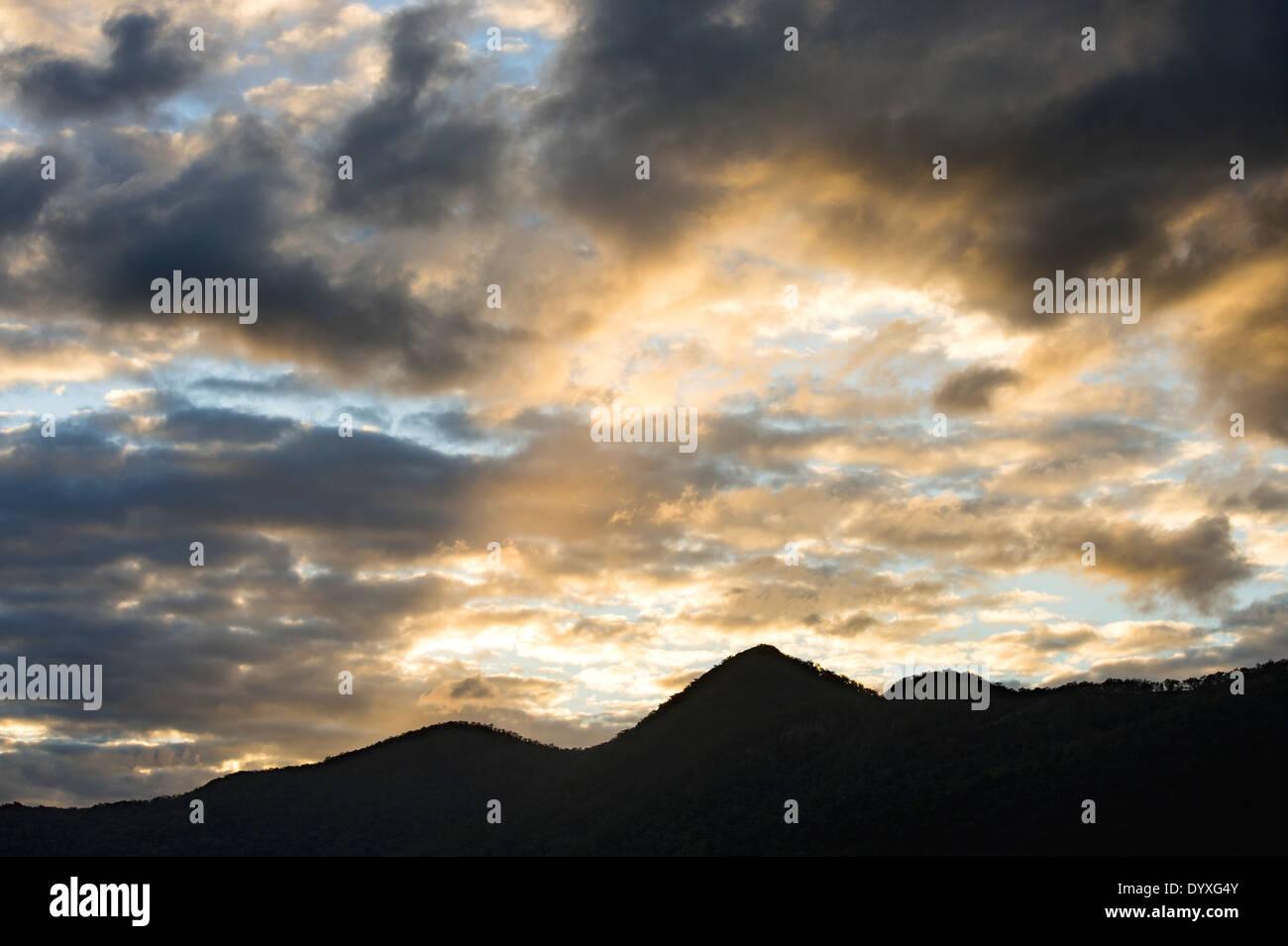 Silhoutted mountain range & sunset sky, QLD Australia Stock Photo