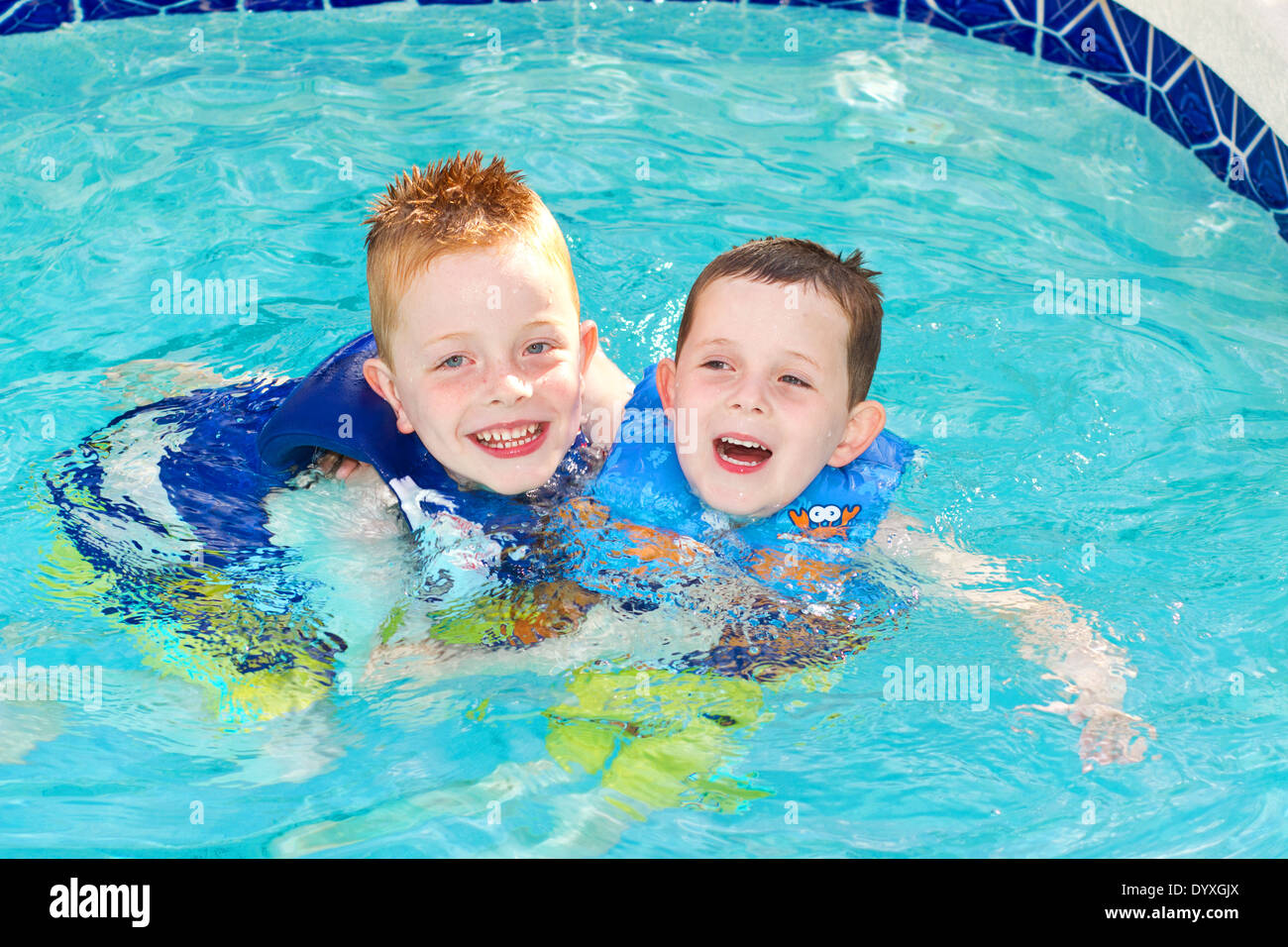 Two Young Boys playing in the swimming pool wearing UV protection ...