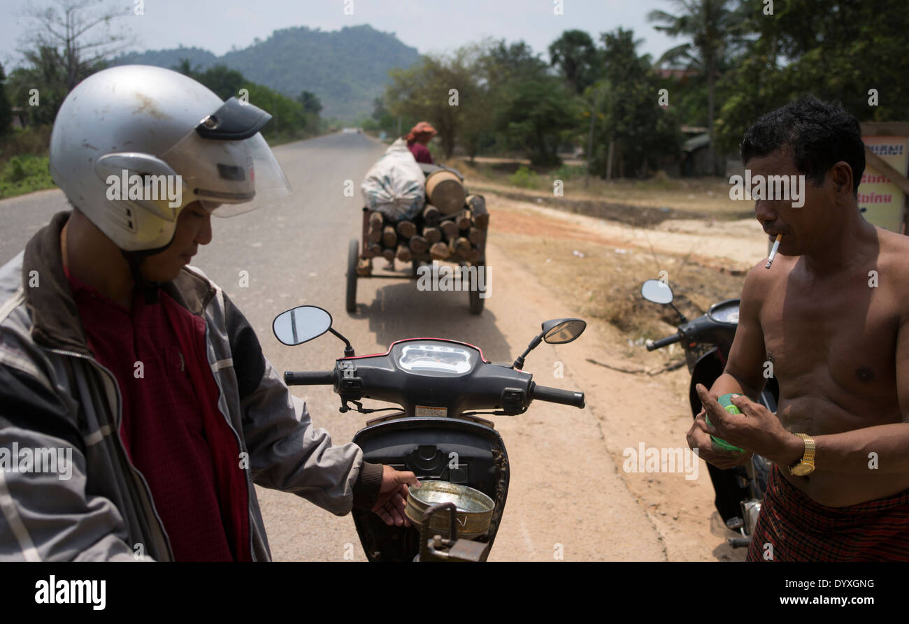 Man smoking while pouring gasoline at Roadside gas station ( gasoline ) Siem Reap, Cambodia - Stock Image