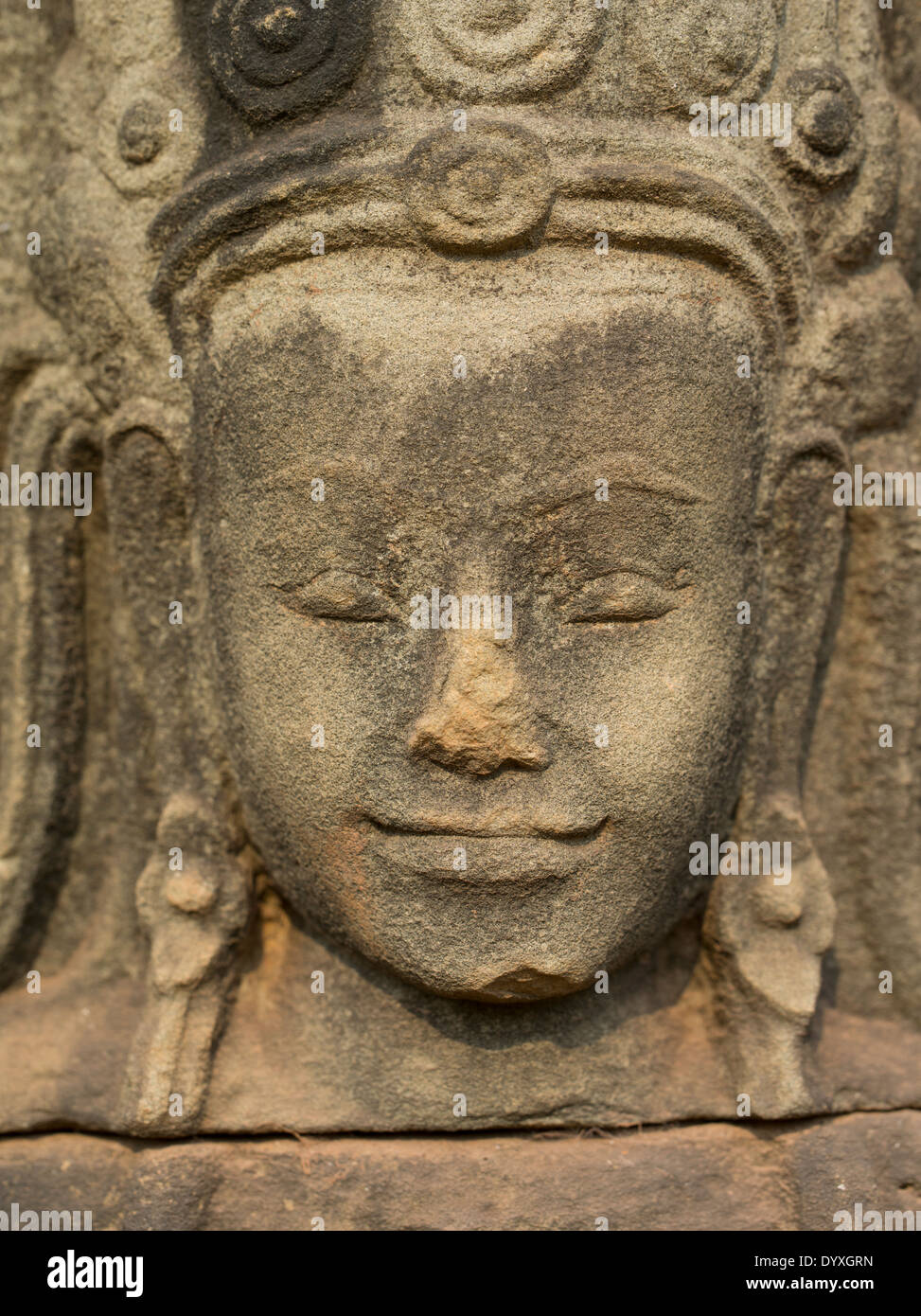 Stone carving of an Apsara face beside the Terrace of Elephants, Angkor Thom Temple, Siem Reap, Cambodia - Stock Image