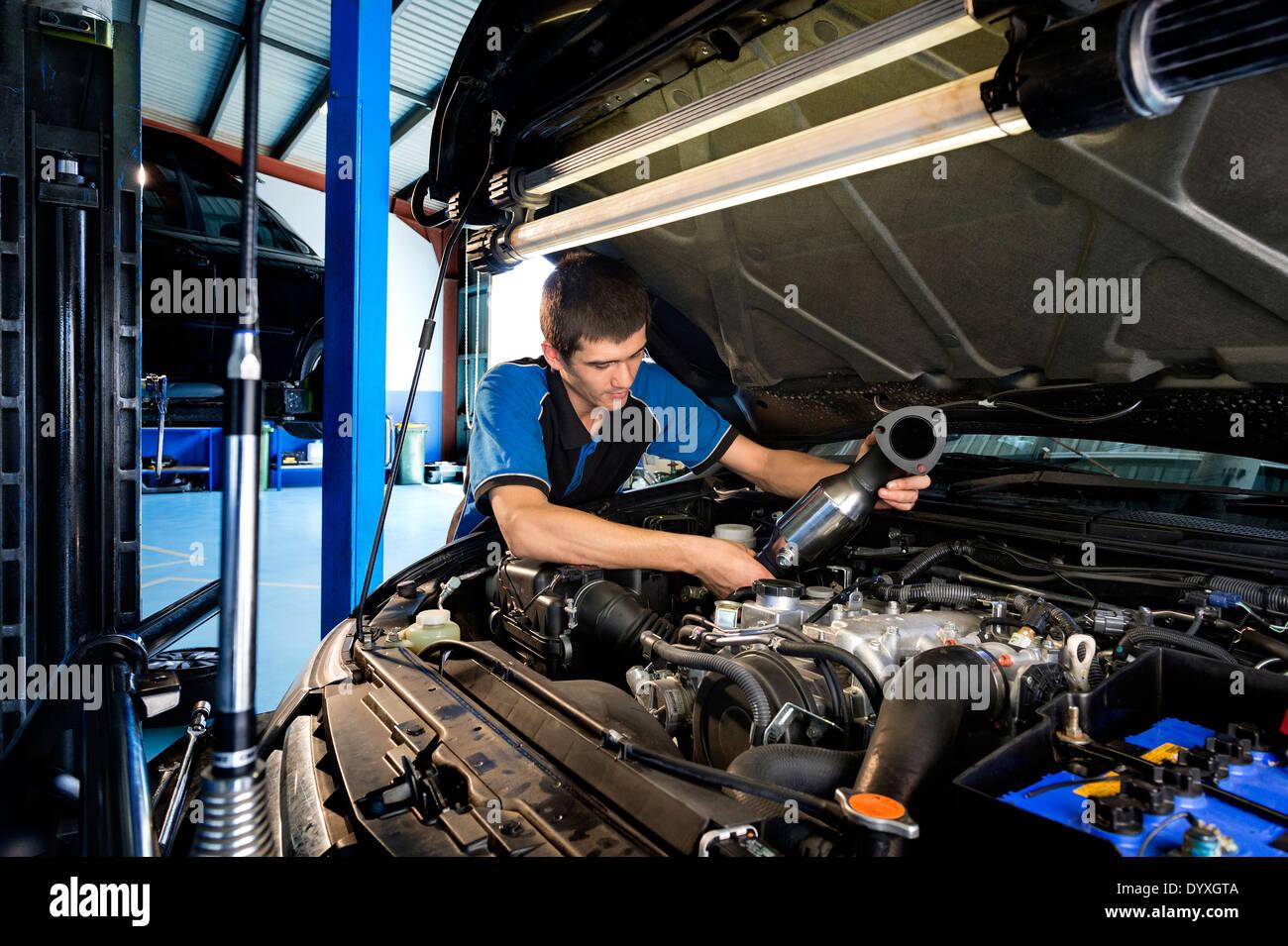 Apprentice mechanic under car hood - Stock Image